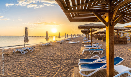 Wall mural Landscape with sunbeds and umbrella on the Red Sea beach at sunrise in Hurghada, Egypt