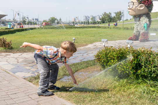 Boy playing with water in sprinkler, in the park. Kid wets his hands in the fountain.