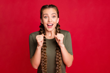 Photo of funny lady long braids raising fists up celebrating best winning football team amazing day wear casual green t-shirt isolated red color background