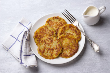 Traditional latkes fritters with sour cream on a light gray textured background, top view