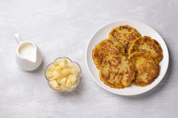 Traditional latkes fritters with sour cream and apple sauce on light gray textured background