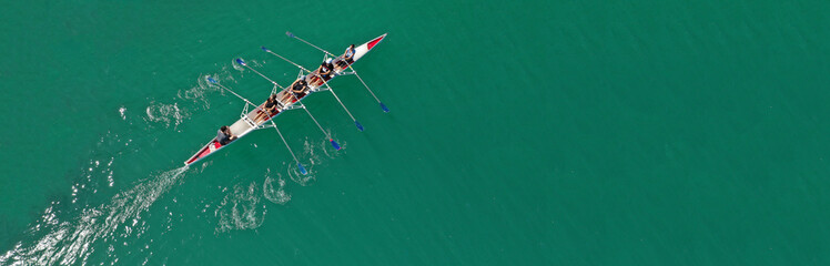 Aerial drone top panoramic view of sport canoe rowing synchronous athletes competing in tropical exotic lake
