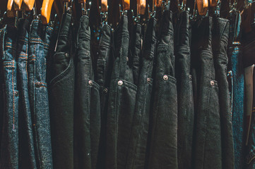 picture of jeans on wooden hangers in a shop under a warm yellow spotlight. moodie feeling.