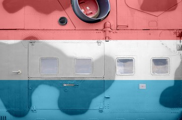 Luxembourg flag depicted on side part of military armored helicopter closeup. Army forces aircraft conceptual background Fotomurales