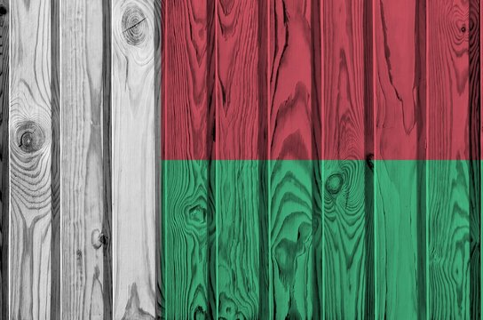 Madagascar flag depicted in bright paint colors on old wooden wall. Textured banner on rough background