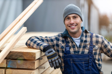 Young male worker in timber warehouse