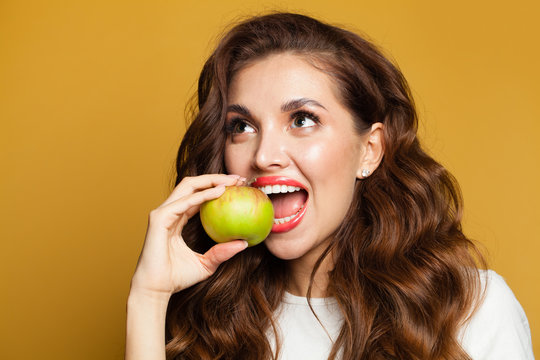 Healthy woman with white teeth biting apple fruit on bright yellow background