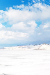 Beautiful winter landscape of frozen Lake Baikal with snowy white hills of Olkhon Island on a February day. Cold light natural background