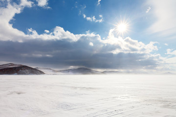 Frequent change of weather characteristic of Baikal Lake, after a blizzard and snowfall, the bright sun shines. View of the Small Sea Strait and Olkhon Island in winter