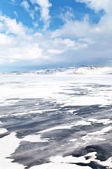 Winds and blizzards typical of winter Lake Baikal. Small Sea Strait and Olkhon Island on a February day. Beautiful winter landscape. Cold natural background