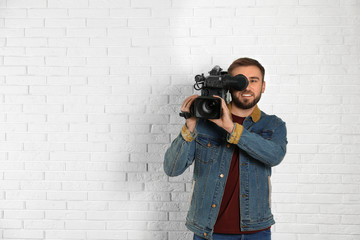 Operator with professional video camera near white brick wall, space for text