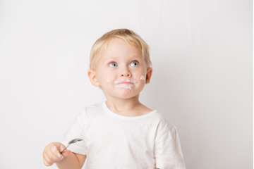 portrait of a blond blue-eyed little caucasian cute boy eating a yogurt with a spoon on a white background