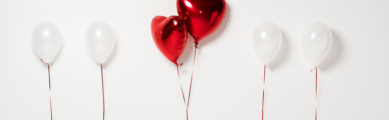 panoramic shot of red heart shaped balloons on white