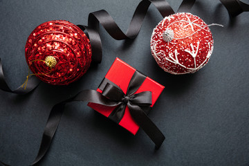 Wall Mural - Christmas present and red xmas balls against black background, Black Friday Christmas concept.