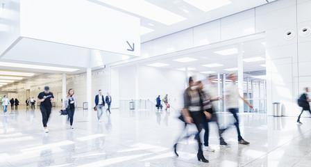 Many trade fair visitors walk under a blank billboard through a hall