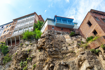 Old houses built on a cliff overhanging a river