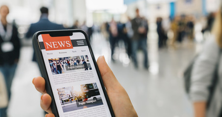 Online news on a mobile smartphone. Close up of businesswoman reading news or articles in a smartphone screen application. Hand holding smart device. Mockup website. Newspaper and portal on internet