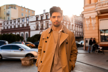 Young handsome casual man in trench coat confidently looking in camera on street Wall mural