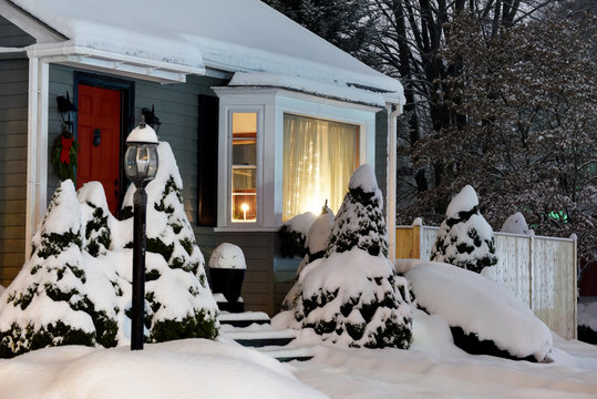 Real Christmas trees festively decorated with New Year and Christmas garlands and toys on the threshold of a simple house on a snowy winter evening. USA. Maine