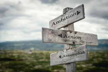 Ambition, action and accomplish  text on wooden rustic signpost outdoors in nature/mountain scenery. Business and lifestyle concept.