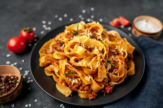 Pasta Bolognese with spices, Italian pasta dish with minced meat and tomatoes in a dark plate on a stone background