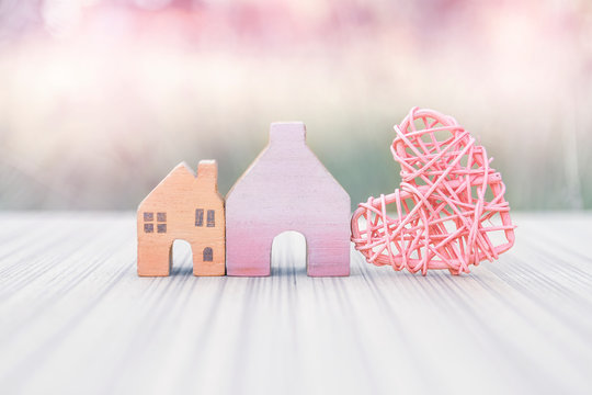 Vintage wooden miniature house with pink wooden heart design over blurred background, vintage filter effect, valentine concept, house and property business