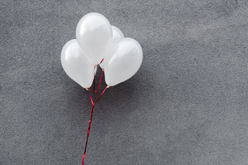 white and decorative balloons on grey with copy space