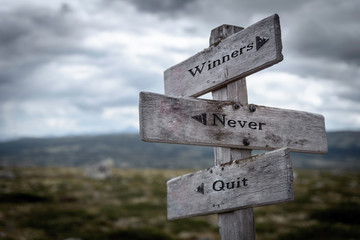 Winners never quit text on wooden rustic signpost outdoors in nature/mountain scenery. Win, fail and success concept.