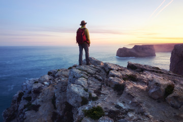 A rear view of of a lone male backpacker or hiker standing on a cliff top with an inspiring ocean view