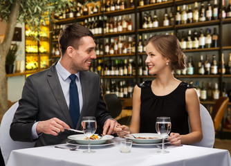 leisure and luxury concept - smiling couple eating main course over restaurant or wine bar...