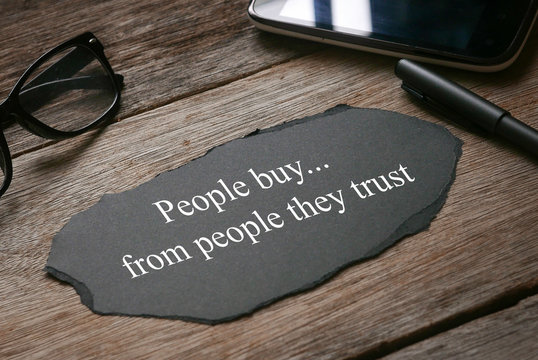 Glasses,mobile phone,pen,a a piece of black paper written with People buy...from people they trust on wooden background.