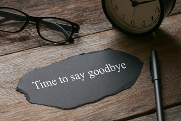 Glasses,clock,pen and a piece of black paper written with Time to say goodbye on wooden background.