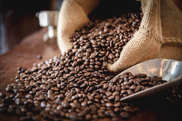 coffee beans in a sack on dark table, top view