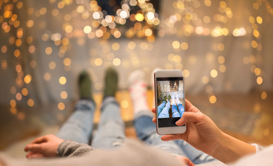 leisure, technology and christmas concept - close up of couple taking foot selfie by smartphone and garland lights at home over shimmering festive lights