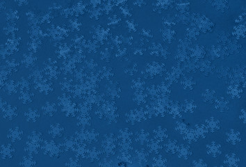 Metallic foil snowflakes confetti sparse on trendy classic blue colored background. Simple holiday concept. Winter festive backdrop. Top view, flat lay. Color of the year 2020.