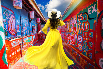 .Asian female tourists visit the old house at Rainbow Village, colorful paintings on the walls in Taichung. It is a famous tourist spot in Taiwan.