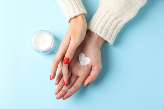 Woman hands, moisturizing cream for clean and soft skin in winter time, jar of cream, sweater, heart shape created from cream on blue background, space for text. Top view. Healthcare concept