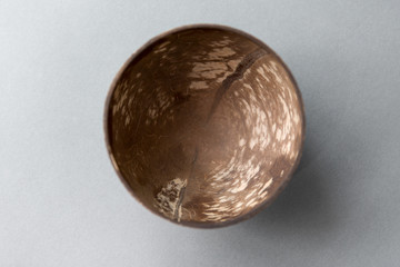 recycling, tableware and eco friendly concept - close up of coconut bowl on table