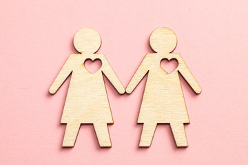 Two lesbian women couple holding hands on pink background