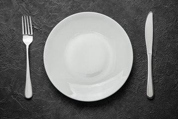 Empty white plate with knife and fork on black table.