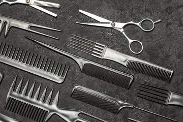 Black combs and combs with scissors on a black background.