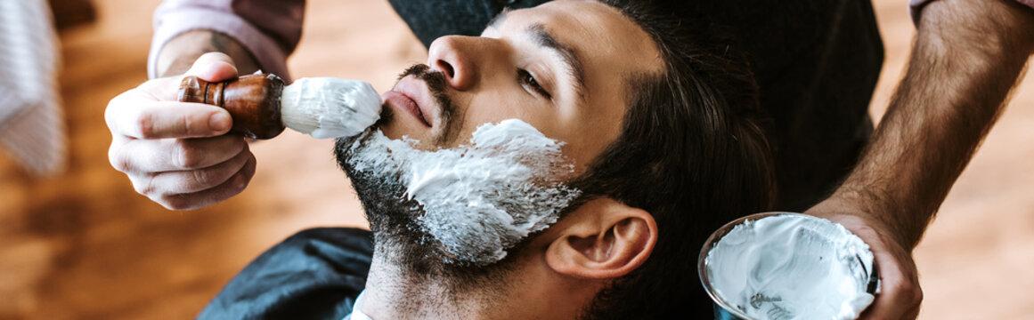 panoramic shot of barber applying shaving cream on face of bearded man