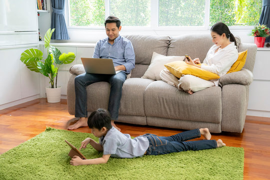 Internet addict concept, Asian parent Each one using private device while together in the living room
