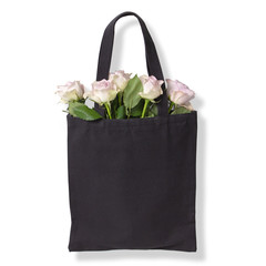 Black cotton tote bag with light violet roses inside. Isolated on white background