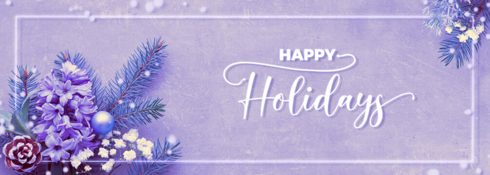 """Top view on purple neon winter background with fir twigs, blue hyacinth flowers, snowflakes and winter herbs. White shiny frame and text """"Happy Holidays"""" with decorative snow."""
