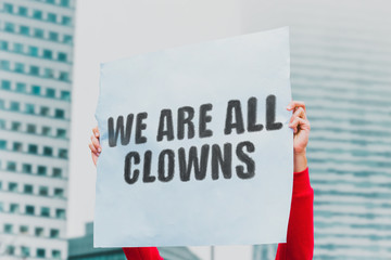 """The phrase """" We are all clowns """" on a paper banner in men's hand. Human holds a cardboard with an inscription. Rally. Protest. Chaos"""