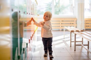 Sweet blonde toddler boy standing in front of a lockers in kindergarden or school hallway