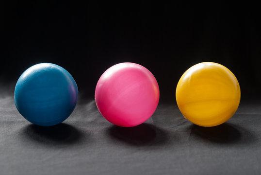 Cyan magenta yellow plastic balls with black fabric background