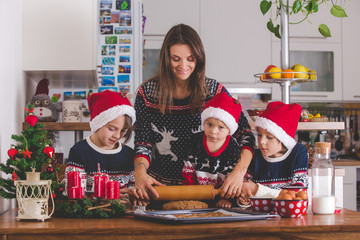 Happy children, boy brothers and mother, baking christmas cookies at home