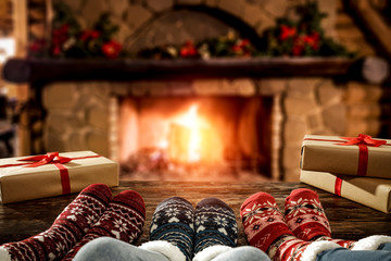 Photo sur Plexiglas The Desk of free space and people legs with christmas socks.Home interior with fireplace and